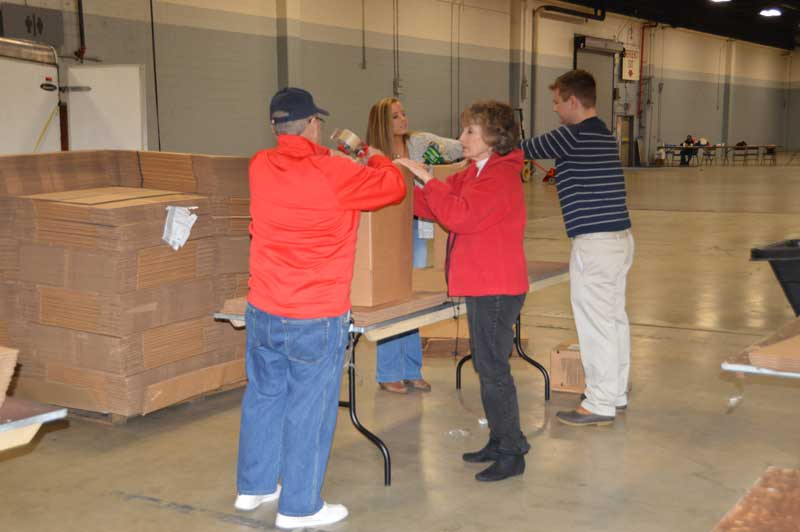 American Legion Post 3 Member Ed Brannen and volunteers from General Electric to tap up boxes that will hold the non-perishable food items.