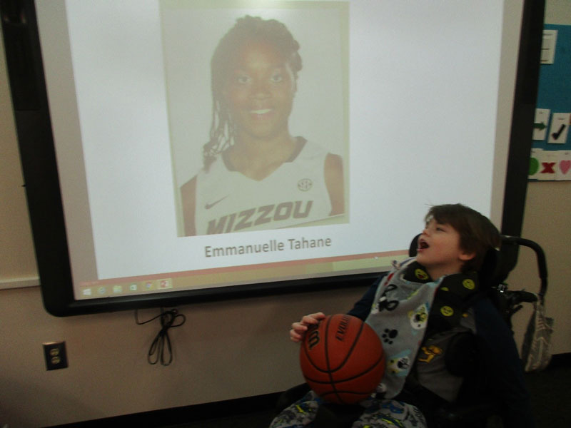 Washington Center student Eliah Peart looks at a picture of his Missouri Women's Basketball team pen pal, Emmanuelle Tahane, as the class discusses college basketball.