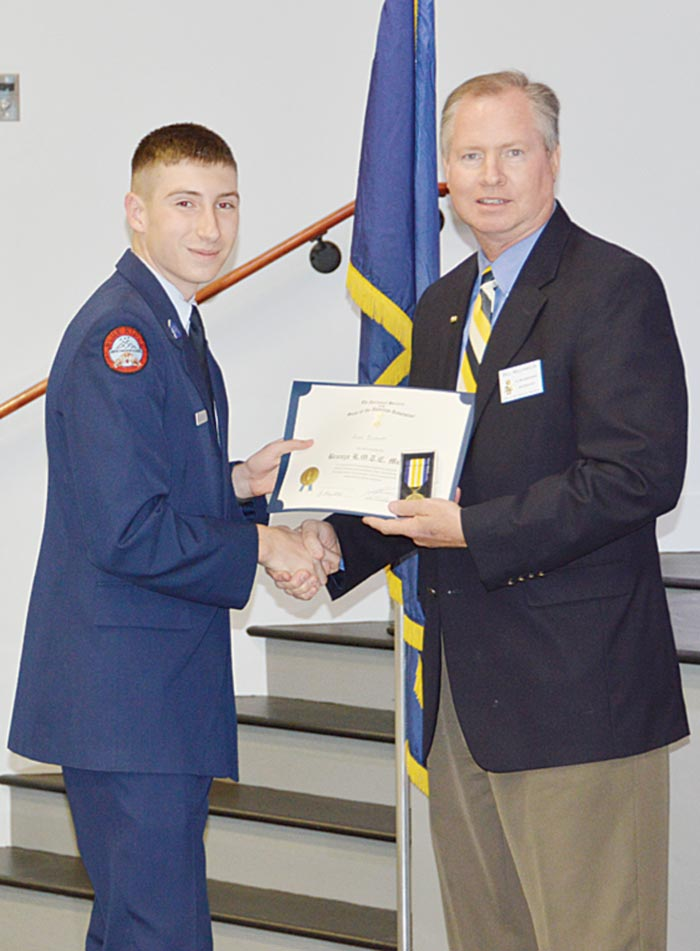 Cadet Aaron Bickett is presented the National Society of the Sons of the American Revolution Certificate and Medal by Bill Williamson.