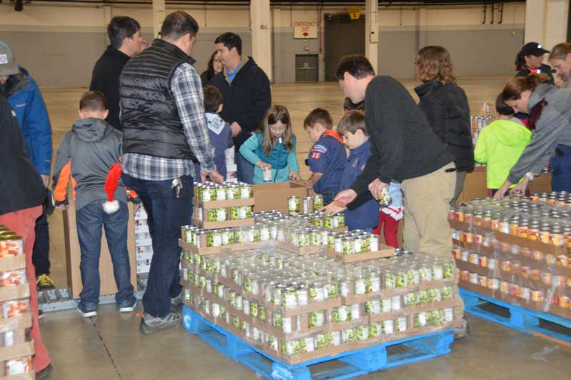 Young volunteers placed canned goods into the food boxes as they moved down the assembly line.